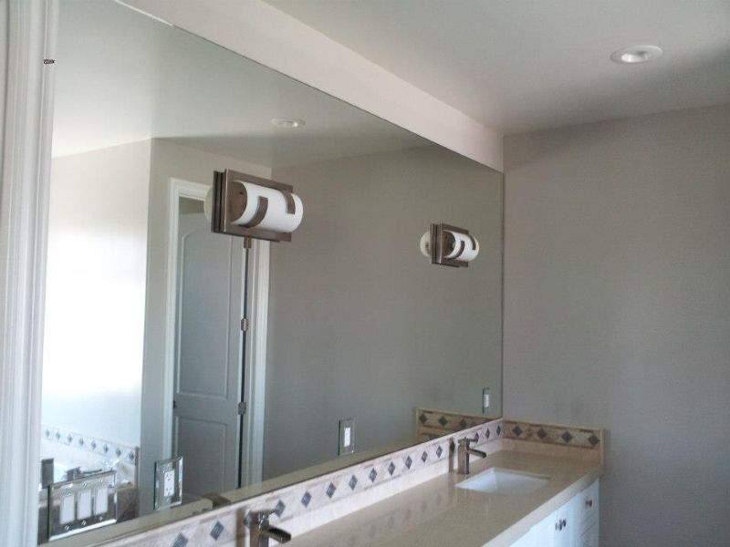 Mirror with cutouts for light fixtures and electrical outlets